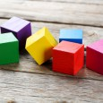 Colorful wooden toy cubes on a grey wooden background