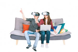 Young Asian couple playing VR virtual reality gadget, sitting on sofa together, isolated on white background. Modern entertainment technology, VDO game devices, or family hobby activity concept