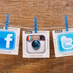 KIEV, UKRAINE - JULY 05, 2015: Popular social media Facebook,Instagram, Twitter hanging on the clothesline on wood background